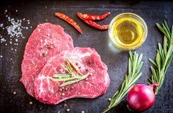 Nya nötköttbiffar med ingredienser på den mörka bakgrunden Royaltyfria Bilder