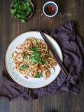 Nya nudlar med räkor, chili, soya, koriander och svartsesam Asiatiska nudlar med räkor, chili och persilja på en vit pl fotografering för bildbyråer