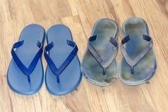 Nya och gamla smutsiga bläddrar misslyckanden på ljust - det bruna golvet Två nya par och slitna ut skor Blåa sandaler på träbakg arkivfoto