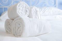 Nya och rena utmärkt hoprullade handdukar ligger på en säng royaltyfri bild