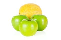 Nya och smakliga äpplen och melon som isoleras på vit Arkivfoto