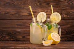 Nya och smakliga drinkar med gult rakt sugrör och citroner, mintkaramell och is på en trätabell Uppfriskande lemonad i exponering Fotografering för Bildbyråer