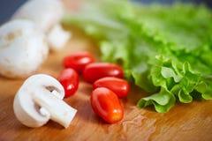 Nya och smakliga tomater, sallad, champignon på skärbräda Fotografering för Bildbyråer