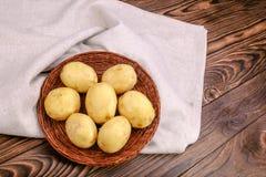 Nya okokta potatisar på en träbakgrund Potatisar i en korg på en säckväv plundrar Näringsrika höstmål kopiera avstånd fotografering för bildbyråer