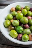 Nya oliv i den vita plattan på den lantliga bakgrunden Royaltyfria Foton