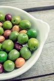 Nya oliv i den vita plattan på den lantliga bakgrunden Royaltyfri Bild