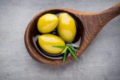 Nya oliv och grå bakgrund Oliv i bunke och sked Arkivfoto