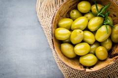 Nya oliv och grå bakgrund Oliv i bunke och sked Royaltyfri Bild