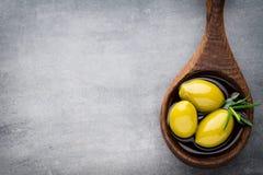 Nya oliv och grå bakgrund Oliv i bunke och sked Arkivfoton