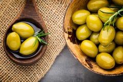 Nya oliv och grå bakgrund Oliv i bunke och sked Arkivbilder
