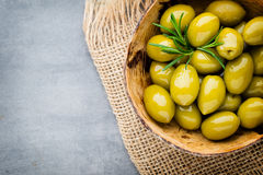 Nya oliv och grå bakgrund Oliv i bunke och sked Royaltyfri Foto