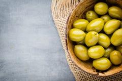 Nya oliv och grå bakgrund Oliv i bunke och sked Royaltyfria Foton