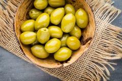 Nya oliv och grå bakgrund Oliv i bunke och sked Arkivbild