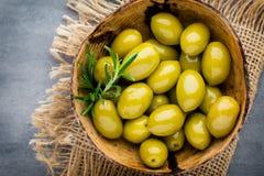 Nya oliv och grå bakgrund Oliv i bunke och sked Fotografering för Bildbyråer
