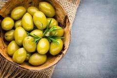 Nya oliv och grå bakgrund Oliv i bunke och sked Royaltyfria Bilder