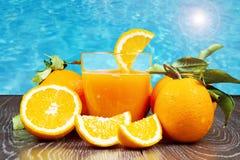 Nya orange fruktsaft och apelsiner på träbakgrund Royaltyfri Foto