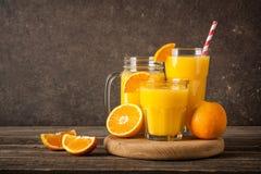 Nya orange fruktsaft och frukter på tabellen Arkivbilder