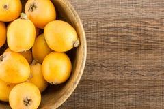 Nya orange japanska loquats på brunt trä Arkivfoton