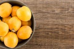 Nya orange japanska loquats på brunt trä Arkivbilder