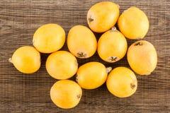 Nya orange japanska loquats på brunt trä Royaltyfria Foton