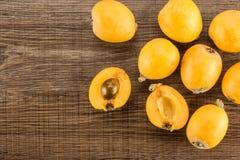 Nya orange japanska loquats på brunt trä Royaltyfria Bilder