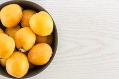 Nya orange japanska loquats på grått trä Royaltyfria Bilder
