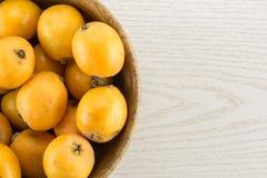 Nya orange japanska loquats på grått trä Arkivfoto