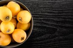 Nya orange japanska loquats på svart trä Royaltyfria Foton