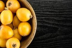Nya orange japanska loquats på svart trä Arkivbilder