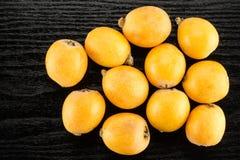 Nya orange japanska loquats på svart trä Royaltyfri Foto