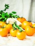 Nya orange tomater, saftiga sommargrönsaker och saftiga gräsplaner Fotografering för Bildbyråer