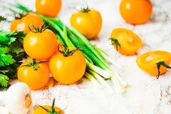 Nya orange tomater, saftiga sommargrönsaker och saftiga gräsplaner Royaltyfri Foto