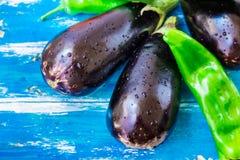Nya organiska aubergine och grön italiensk peppar med vattendroppar på blå wood bakgrund, ljusa färger, vegetariskt rent äta Arkivbilder