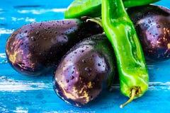 Nya organiska aubergine och grön italiensk peppar med vattendroppar på blå wood bakgrund, ljusa färger, vegetariskt rent äta Royaltyfria Foton