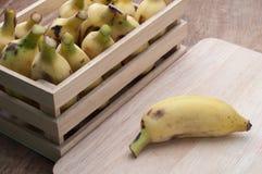 Nya organiska bananer på träbakgrund arkivfoto