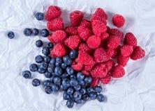 Nya organiska blåbär och hallon på skrynkligt papper Rich med vitaminer Arkivfoto