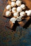 Nya organiska champinjoner på tappningskärbrädan, lodlinje Royaltyfri Bild