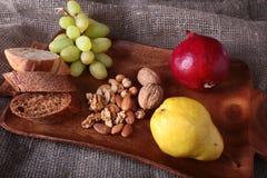 Nya organiska frukter på det wood portionmagasinet Det blandade äpplet, päronet, druvor, torkade frukter och muttrar Royaltyfria Bilder