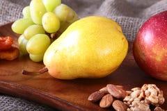 Nya organiska frukter på det wood portionmagasinet Det blandade äpplet, päronet, druvor, torkade frukter och muttrar Royaltyfri Foto
