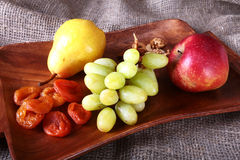 Nya organiska frukter på det wood portionmagasinet Det blandade äpplet, päronet, druvor, torkade frukter och muttrar Fotografering för Bildbyråer