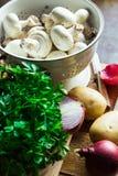 Nya organiska grönsaker, champinjoner, potatisar, lökar, persilja på köksbordet Arkivbild