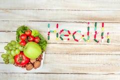 Nya organiska grönsaker och frukter på plattan med det vård- ordet som göras av preventivpillerar på träyttersida Arkivbilder