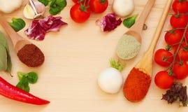 Nya organiska grönsaker och träskedar med kryddor royaltyfri foto