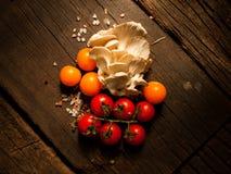 Nya organiska grönsaker på en texturerad trätabell med solljus Royaltyfri Foto