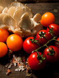 Nya organiska grönsaker på en texturerad trätabell med solljus röda tomater Royaltyfria Foton