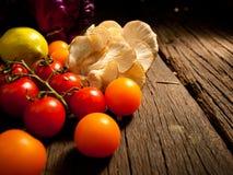 Nya organiska grönsaker på en texturerad trätabell med solljus Varmt ljus och trätexturer Arkivbilder