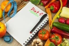 Nya organiska grönsaker på tabellen Banta mål Rått banta Planera ett sunt banta Dagbok av ett bantaplan Gårdsprodukter arkivbilder
