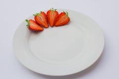 Nya organiska jordgubbar med gröna sidor som halveras och dekoreras på en vit platta Royaltyfria Foton