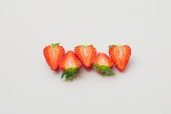 Nya organiska jordgubbar som halveras och som är ordnade på en vit bakgrund Arkivfoton