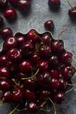 Nya organiska körsbär i metallbunke på mörk stenbakgrund Royaltyfri Bild